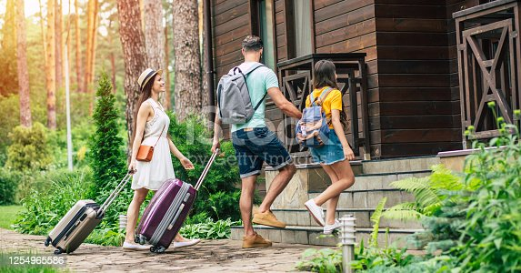 At last, hotel. A photo with sunny light effect of a glad family with suitcases and backpacs on a weekend coming to the hotel surrounded by trees, father holding his daughter's hand.