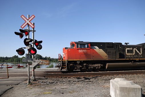 Maple Ridge, Canada - May 16, 2021: Red warning lights flash as CN 8810 heads east at the 225th Street level crossing in Maple Ridge. Background shows the Fraser River flowing through Metro Vancouver in springtime.
