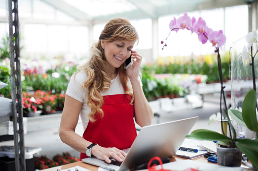 Beautiful mature female , smiling works at garden centre retail store.Taking orders over the phone. She working at table and in background  is a shop with lots of flowers