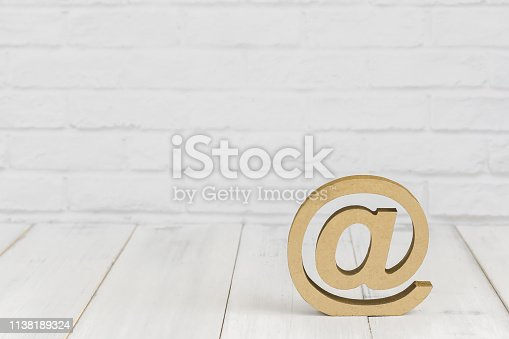 istock At sign on white wood table over white brick background with copy space. 1138189324