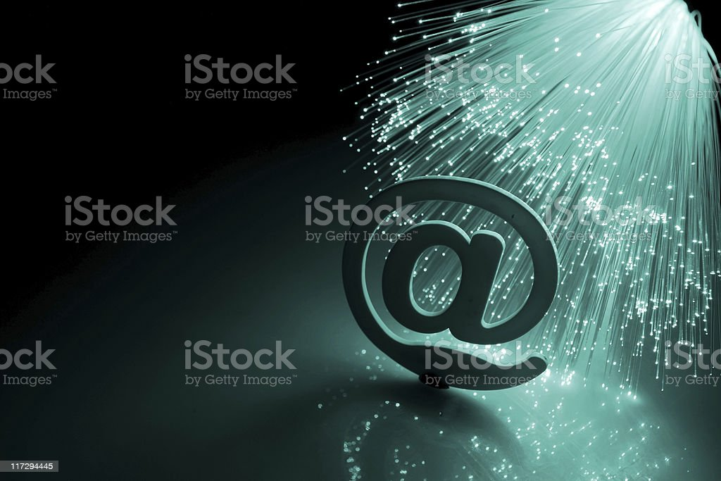 A 3D At sign with fibre optic cable behind it stock photo