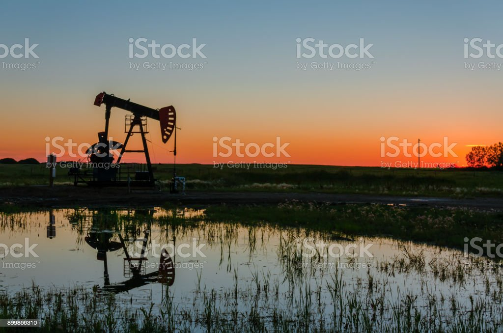 At sunset, oil pumps pump oil on a black field. stock photo