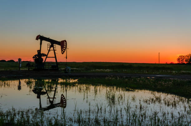 at sunset, oil pumps pump oil on a black field. - land vehicle stock photos and pictures
