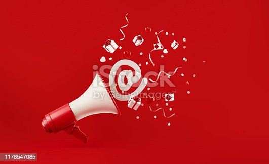 istock At Symbol Coming Out of  A Megaphone with Gift Boxes Paper Confetti and Party Streamers Falling on Red Background 1178547085