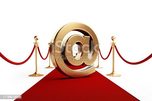 Gold colored at symbol standing on a red carpet isolated on white background. Horizontal composition with clipping path and copy space. Great use for first class customer relations concepts.