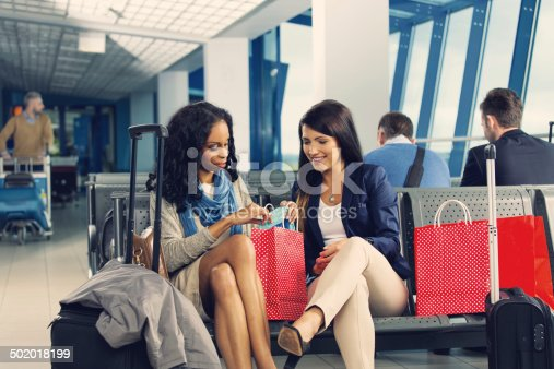 People waiting for a flight at the airport lounge. Focus on the two women talking and watching their purchases of duty free.