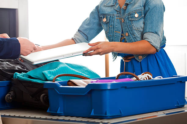 At the airport security checkpoint Close up of woman's hands putting a laptop into a box at airport security check. security barrier stock pictures, royalty-free photos & images