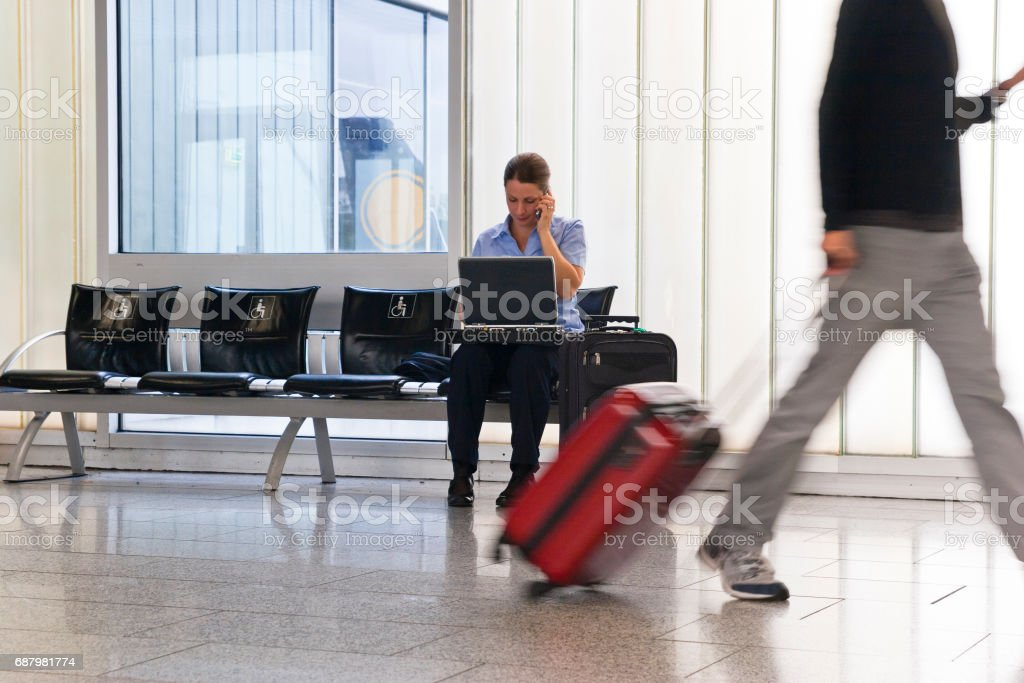 At the airport stranded business woman using mobile phone and laptop. stock photo