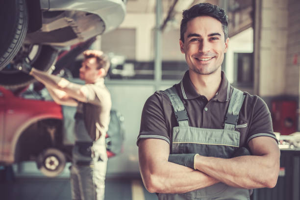 At the auto service At the auto service. Handsome young auto mechanic in uniform is looking at camera and smiling while his colleague is examining car repairman stock pictures, royalty-free photos & images
