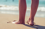 Woman's feet standing at the beach