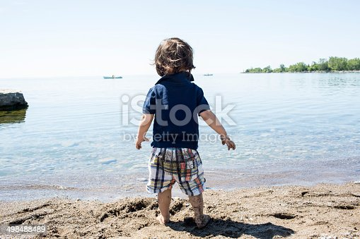 Little boy with bare feet in the sand looking out at the water while at the beach