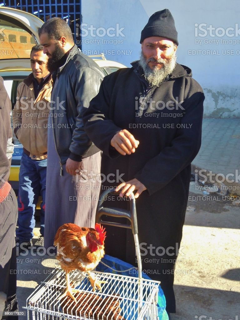 At the bird and animal market in Tunis, Tunisia. A man offers a splendid rooster for sale. stock photo