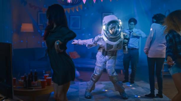auf der college house costume party: fun guy wearing space suit dances off, doing robot dance modern moves. mit ihm schöne mädchen und jungen tanzen in neon lichter. - faschingskostüme herren stock-fotos und bilder