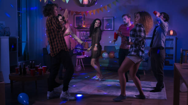 at the college house party: diverse group of friends have fun, dancing and socializing. boys and girls dance in the circle. disco neon strobe lights illuminating room. - disco lights stock pictures, royalty-free photos & images