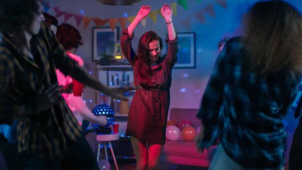 na college house party: young girl dances w środku kręgu ludzi. zróżnicowana grupa przyjaciół baw się dobrze, tańczy i towarzysko. disco neon strobe światła oświetlenie pokój. - impreza zdjęcia i obrazy z banku zdjęć