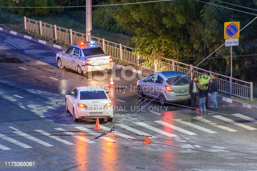 684793794istockphoto At the crossroads at night, the driver violated and knock down a pedestrian. The police draw up a road traffic accident. Police inspector car with emergency flashing lights. 1173365061