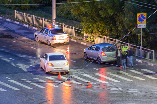 684793794 istock photo At the crossroads at night, the driver violated and knock down a pedestrian. The police draw up a road traffic accident. Police inspector car with emergency flashing lights. 1173365061