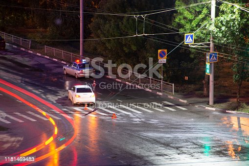 684793794istockphoto At the crossroads at night, the driver violated and knock down a pedestrian. The police draw up a road traffic accident. Police inspector car with emergency flashing lights. 1181469483