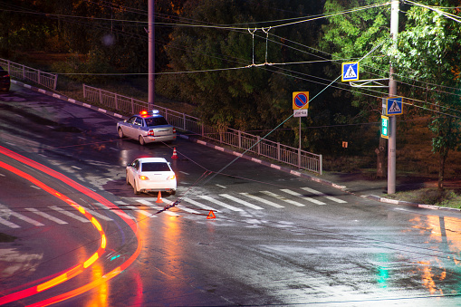 684793794 istock photo At the crossroads at night, the driver violated and knock down a pedestrian. The police draw up a road traffic accident. Police inspector car with emergency flashing lights. 1181469483