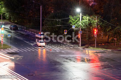 684793794istockphoto At the crossroads at night, the driver violated and knock down a pedestrian. The police draw up a road traffic accident. Police inspector car with emergency flashing lights. 1186662647