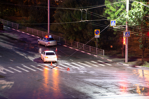 684793794 istock photo At the crossroads at night, the driver violated and knock down a pedestrian. The police draw up a road traffic accident. Police inspector car with emergency flashing lights. 1205053141