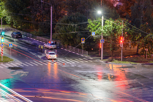 istock Ulyanovsk, Russia - April 10, 2020. At the crossroads at night, the driver violated and knock down a pedestrian. The police draw up a road traffic accident. Police inspector car with emergency flashing lights. 1226990230