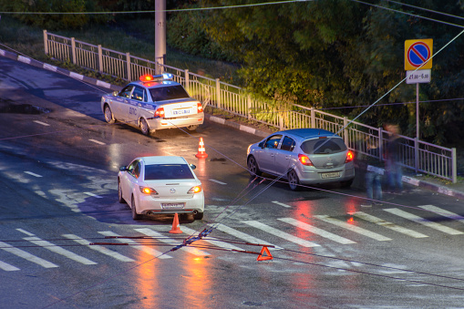 684793794 istock photo At the crossroads at night, the driver violated and knock down a pedestrian. The police draw up a road traffic accident. Police inspector car with emergency flashing lights. 1247245534