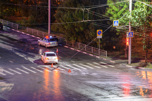 684793794 istock photo At the crossroads at night, the driver violated and knock down a pedestrian. The police draw up a road traffic accident. Police inspector car with emergency flashing lights. 1249426601