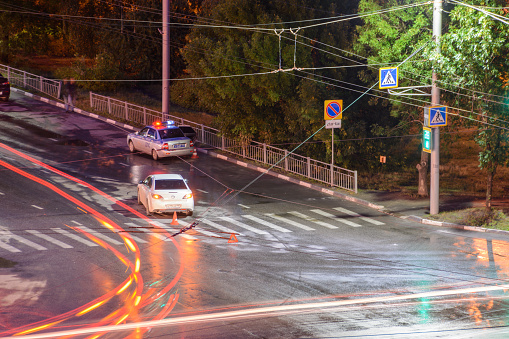 684793794 istock photo At the crossroads at night, the driver violated and knock down a pedestrian. The police draw up a road traffic accident. Police inspector car with emergency flashing lights. 1256129390