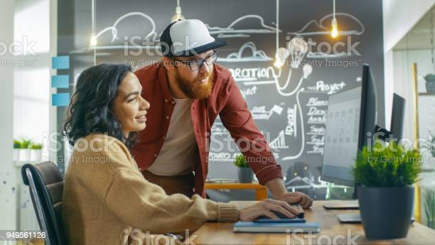At The Desk Beautiful Woman Developer Talks With Programer Together They Design New Mobile Game Application They Work In The Stylish Indie Creative Studio Stock Photo - Download Image Now
