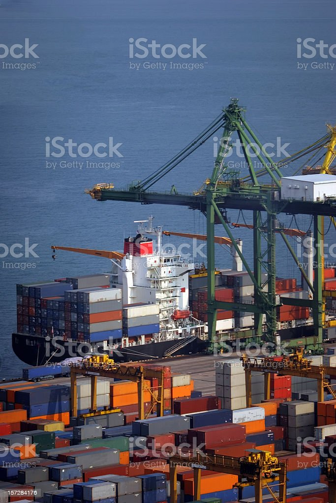 At the dock: containers and ship, just in time royalty-free stock photo