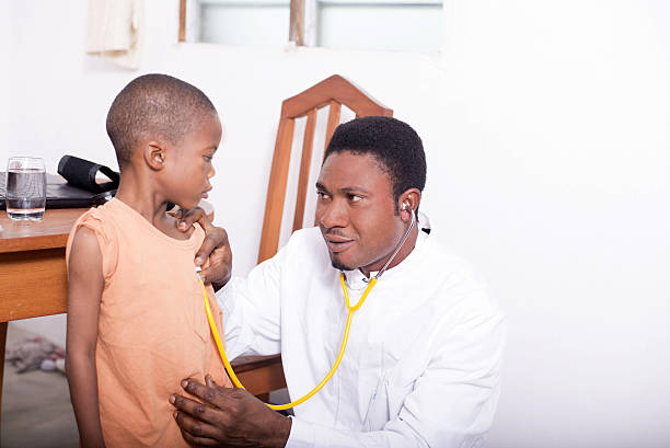 At the doctor the doctor is consulting the child within the framework of mandatory consultations of children côte d'ivoire stock pictures, royalty-free photos & images