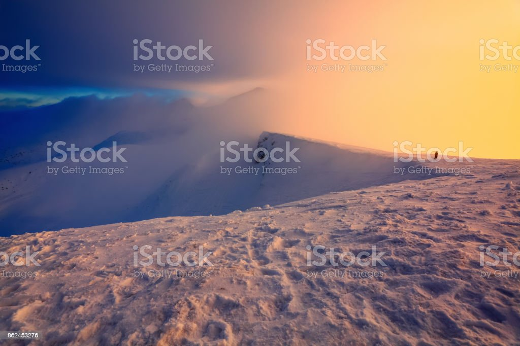 At the edge of the snowy rock someone is standing. The high mountains in the fog, morning sky is enlighten with the orange colored light in winter day. stock photo