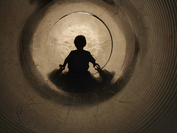 At The End of a Tunnel: Boy on Slide stock photo