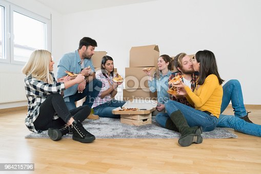 Group of friends sitting on the carpet and taking a break for pizza while moving into new apartment.