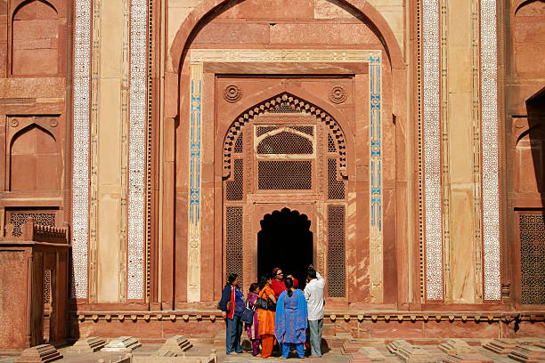 At the entrance Fathehpur Sikri (India) - December 27, 2005: Group of Indian women in saris are standing in front of the tomb within the Jama Masjid\'s courtyard and listening to male tourist guide. agra jama masjid mosque stock pictures, royalty-free photos & images