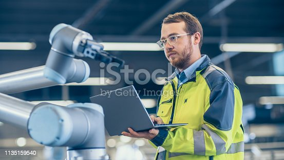 istock At the Factory: Automation Engineer Uses Laptop for Programming Robotic Arm. New Era in Automatic Manufacturing Industry. 1135159540
