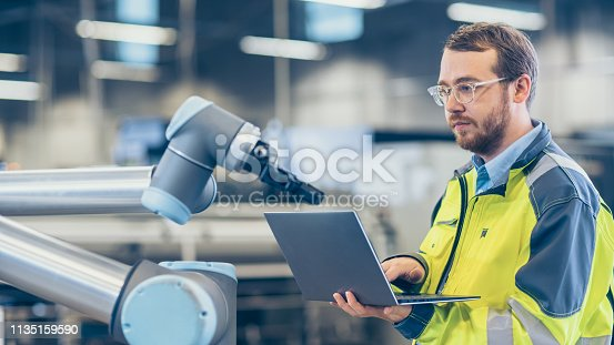 istock At the Factory: Automation Engineer Uses Laptop for Programming Robotic Arm. New Era in Automatic Manufacturing Industry. 1135159590