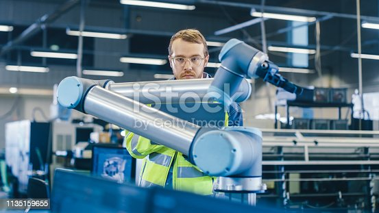 istock At the Factory: Automation Engineer Uses Laptop for Programming Robotic Arm. New Era in Automatic Manufacturing Industry. 1135159655