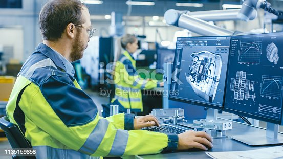 istock At the Factory: Mechanical Engineer Works on Computer, Designs in CAD 3D Model of the Engine. In the Background Factory Workers and Manufacturing Process. 1135159658