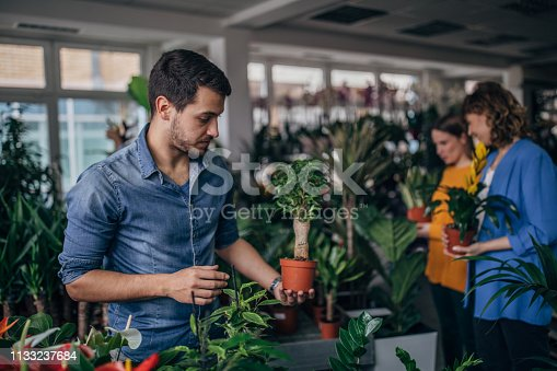 Three people are at the flower shop, holding plants.