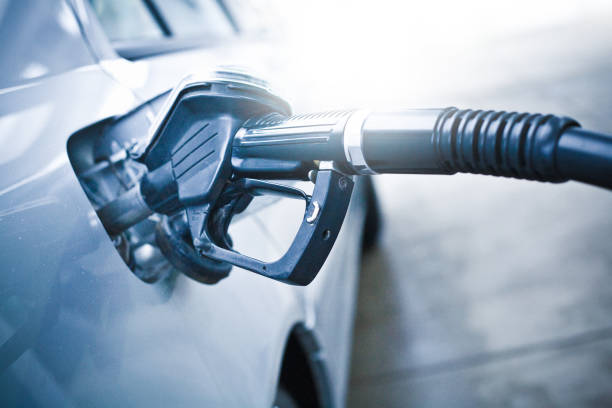 en la gasolinera repostar el coche - echar combustible fotografías e imágenes de stock