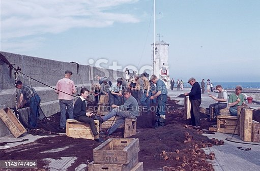 Edinburgh, Scotland, UK, 1965. At the harbor of Edinburgh. Fisherman mending and gathering their fishing nets at the pier. Furthermore: tourists and a lighthouse.