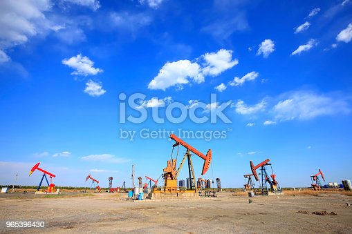 At the oil field, the oil pump is running, blue sky and white clouds. Timelapse