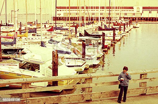 Vintage photo of a boy in the pier at San Francisco during a tirp in the eighties.