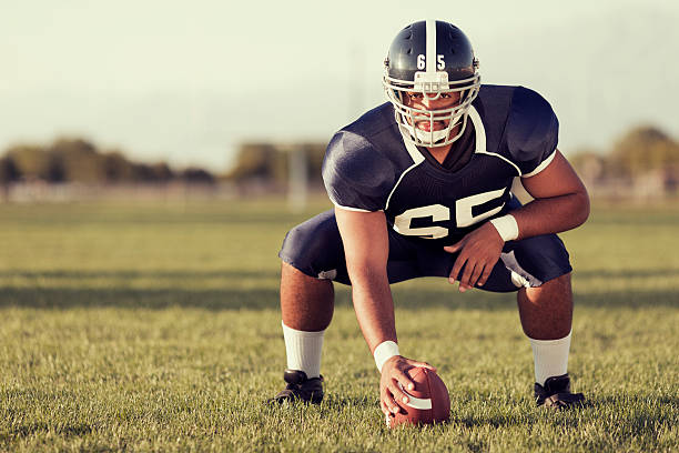 At the Ready A center is ready to snap the ball playing American Football. football lineman stock pictures, royalty-free photos & images