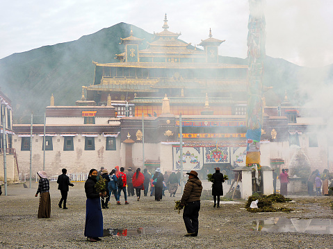 At the Buddhist monastery of Samye, near Tsedang, on a cloudy day. Samye is the most ancient monastery in Tibet. The photo shows people gathering at the monastery on the occasion of the annual celebrations. The smoke, visible in the picture, is generated by the burning of small juniper branches, as traditional ritual offerings by the pilgrims.