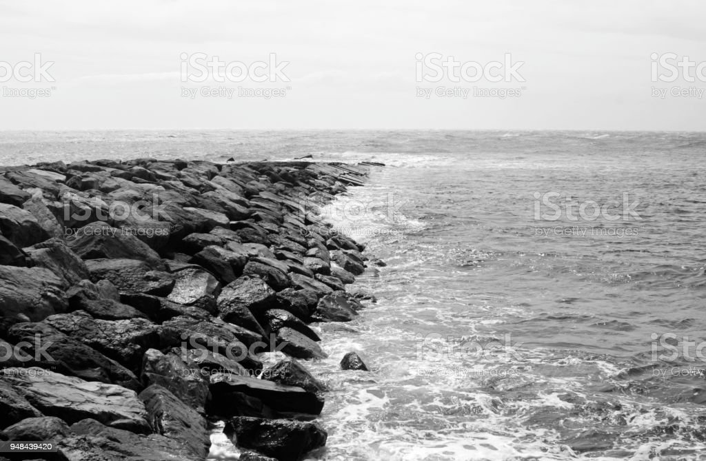 at the sea, water and stones, black-and-white