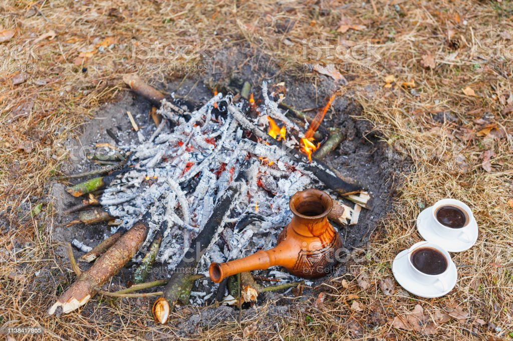 At the stake in the spring forest, a clay Turkish coffee pot is...