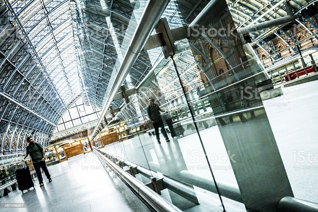 At the Station A tourist with wheelie suitcase at the railway station. Architecture Stock Photo